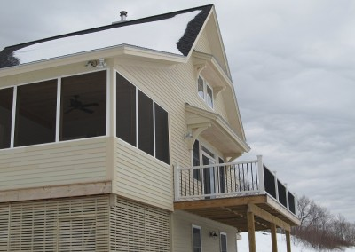 From this angle, we see a nice deck off the great room and a screened in porch to keep summer pests at bay.