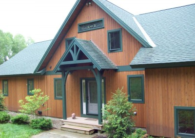 Simple timber entry and stained glass window are featured in this Mt Holly Vt home.