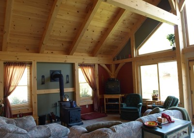 Simple lake front living room in a ranch style designed timber frame