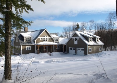 The design of this Stratton Vt home has matching shed dormers on the garage and house