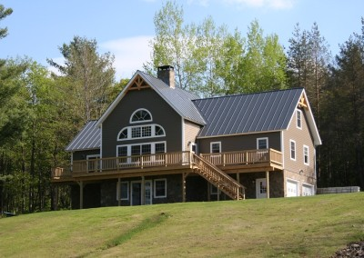 This Wilmington Vt home features a stone chimney,plenty of window area to enjoy the view, and large deck to relax on.