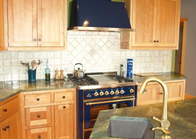 Very high end kitchen featuring midnight blue stove and range hood